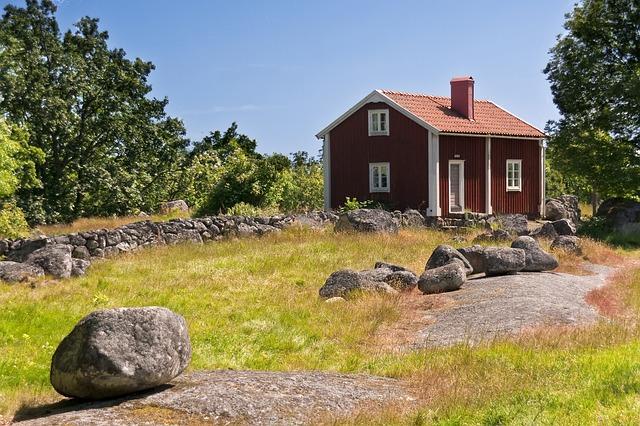 červenobílý domek, tráva, kameny